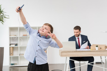 Boy taking self portrait while his father businessman working in office