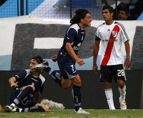 Racing Club's Luguercio celebrates after scoring past River Plate's Fernandez in Buenos Aires