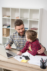 Businessman freelancer working at table with son at home office