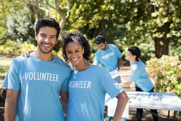 Smiling volunteers standing in the park