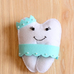 Felt tooth fairy doll isolated on wooden background. Cute felt tooth fairy for small kids. Handmade children's stuffed toy idea. Top view. Closeup