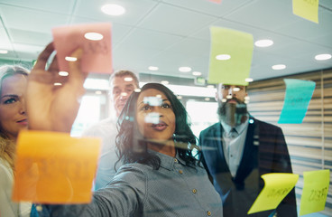 Businesswoman putting sticky note on glass