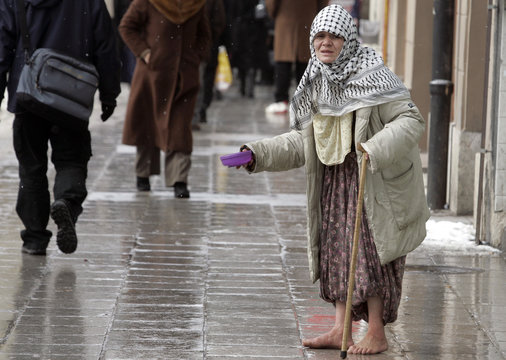 A barefoot woman begs for money as snow falls in central Sarajevo