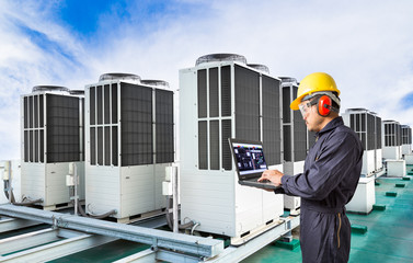 Electrical engineer using laptop computer for maintenance air conditioning system on rooftop of factory