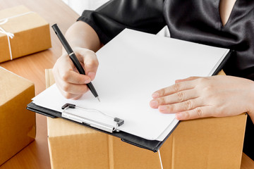 Woman signs clipboard for delivery
