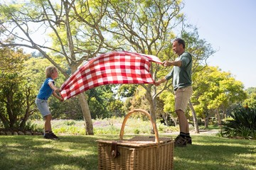Fotorollo Picknick Father and son spreading the picnic blanket