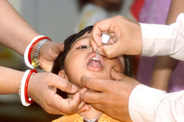 A DOCTOR ADMINITERS POLIO DROPS TO A CHILD IN NEW DELHI.