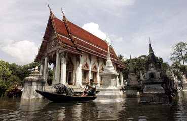 A Thai villager uses a boat to cross a flooded temple in Ayutthaya province