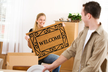 Moving: Woman Holds Welcome Mat On Moving In Day