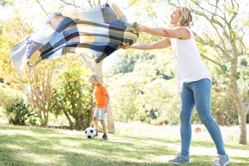 Mother spreading the picnic blanket while son playing football i