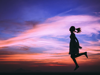 Silhouette of free woman enjoying freedom feeling happy at sunset. relaxing woman in pure happiness