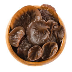 Fresh black fungus in wooden bowl. Auricularia auricula-judae, also known as Jew's ear, wood and jelly ear, and Mu Err. Ingredient in Chinese dishes. Macro food photo close up from above over white.