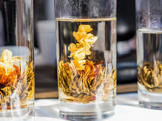 herbal flower hot tea on transparent glass in process, aroma beverage for refresh and health in the morning