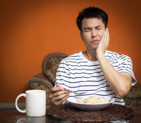 asian man has a hypersensitive teeth and toothache while eating.