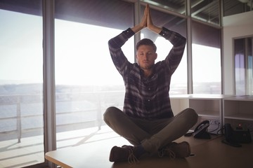 Young businessman meditating on table at office