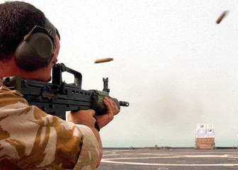 BRITISH SOLDIER TESTS HIS WEAPON ON BOARD WARSHIP IN GULF.