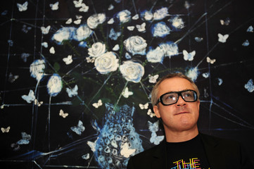"""British artist Damien Hirst poses for photographers in front of his painting """"White Roses and Butterflies"""" in London"""