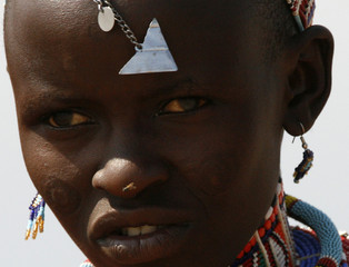 A Maasai woman spots traditional beads during a dance in front of tourists in Amboseli national park