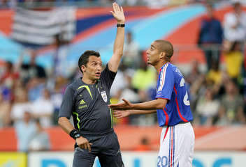 France's Trezeguet gestures next to referee Larrionda of Uruguay during their Group G World Cup 2006 soccer match against Togo in Cologne