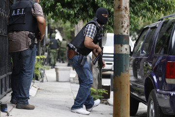 Members of the investigative police force take cover during a gunfight with drug hitmen in Monterrey