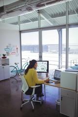 Confident female designer using digitizer on desk in office