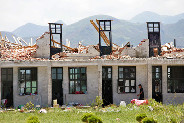 A local resident walks past a house, destroyed by Typhoon Saomai in eastern province of Zhejiang