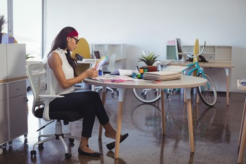 Young businesswoman working while sitting at desk in office