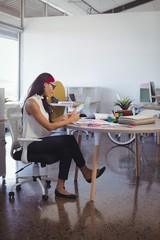 Businesswoman working while sitting at desk in office