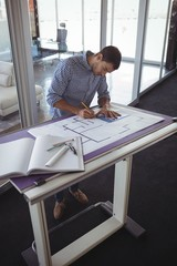 Focused interior designer planning on paper in creative office