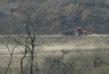 Farm tractor moves along a road in Gijungdong propaganda village, North Korea, in this picture taken from South Korean observation post at truce village of Panmunjom in DMZ separating two Koreas in Paju