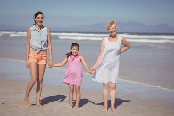 Portrait of happy multi-generation family holding hands at beach