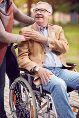 Disabled positive elderly man in wheelchair .