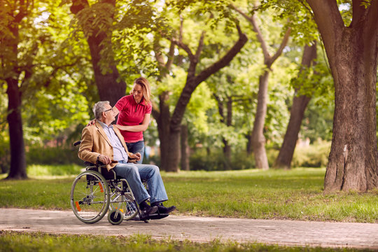 senior man in wheelchair in the park with daughter.