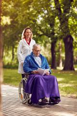 smiling nurse pushing elderly man in wheelchair while reading book .