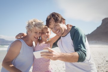Happy multi-generated family taking selfie at beach