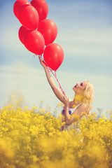 Girl in yellow field letting go of a bunch of balloons
