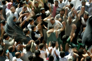 IRAQI SHI'ITE MUSLIMS SLAP THEMSELVES ON THE CHEST TO MARK THE END OF THE PROCESSION TO THE HOLY SHRINE OF IMAN HUSSEIN AT THE AL HUSSEIN MOSQUE IN KERBALA
