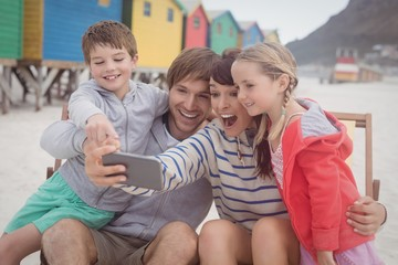 Cheerful family taking selfie at beach