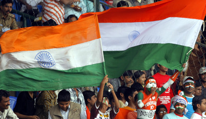 Indian cricket fans wave national flags during the fifth day of the third and final test cricket match against Pakistan in Bangalore