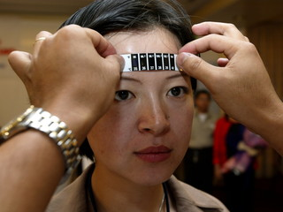 A HEALTH WORKER TAKES THE TEMPERATURE OF A CHINESE DELEGATE DURING A SARS FORUM IN PAMPANGA PROVINCE NORTH OF MANILA