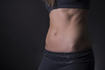 Female abdominal muscles on black background