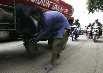 A youth taps oil from a fuel truck along a street in Jakarta