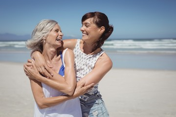 Happy woman with her mother standing at beach
