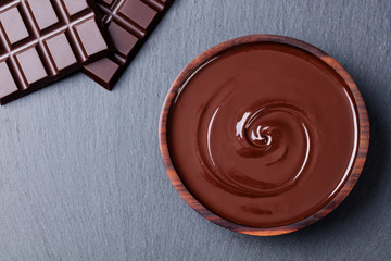 Melted chocolate and bar chocolate. Slate background. Copy space Top view