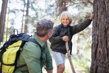 Boy looking at father while standing by tree trunk