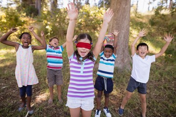 Friends with blindfolded girl cheering in forest