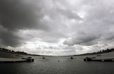 Competitors row under dark clouds during heat at World Rowing Championships in Eton