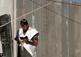 AN ISRAELI BORDER POLICEMAN PRAYS IN FRONT OF CONCRETE WALL SEPARATING THE WEST BANK VILLAGE OF ABU ...