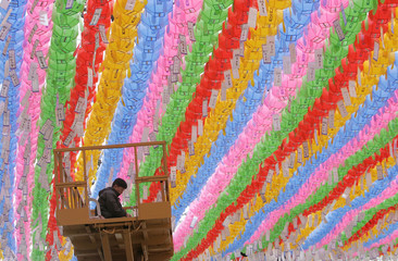 A worker attaches name cards to lotus lanterns in preparation for upcoming celebrations to commemorate the birthday of Buddha, at the Chogye temple in Seoul