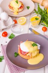 Eggs Benedict for breakfast on white wooden background